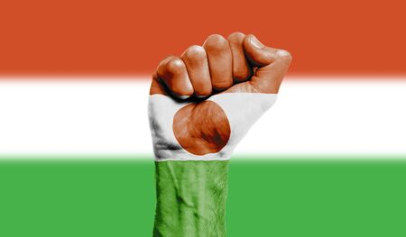 Niger flag painted on a clenched fist. Strength, Protest concept