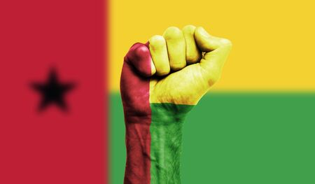 Guinea Bissau flag painted on a clenched fist. Strength, Protest concept
