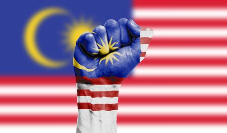 Malaysia flag painted on a clenched fist. Strength, Protest concept