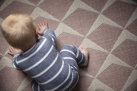 A young baby crawling. Overhead lifestyle baby development