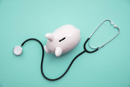 Cost of healthcare. Piggy bank money box with a medical doctors stethoscope Archivio Fotografico