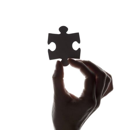 Silhouette of a hand holding a jigsaw puzzle piece on a white background