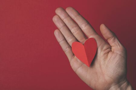 Female hand holding a red paper cut out heart on a plain red background.