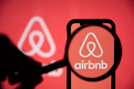 LONDON, UK - May 15 2020: Airbnb home rental logo under a magnifing glass