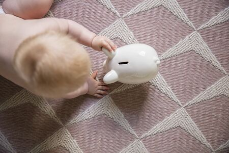 Overhead view of a baby reaching for a piggy bank savings box