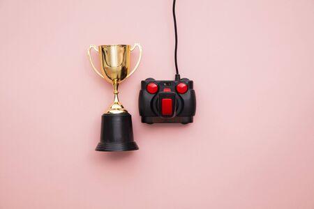 winning gamer. A retro games joystick with a gold winning trophy