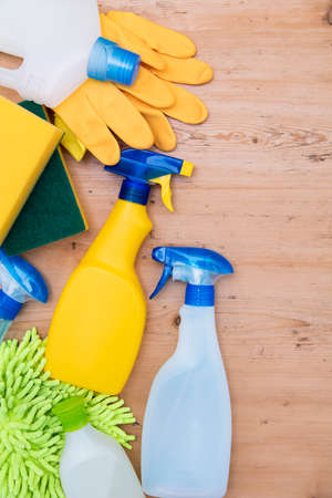 Cleaning spray bottles and cloth lay flat composition on a wooden background
