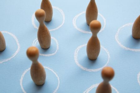 Social distancing concept. Wooden figures stand in white circles