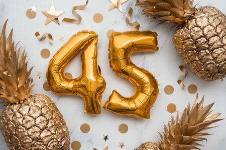 45th birthday celebration card with gold foil balloons and golden pineapples. 스톡 콘텐츠