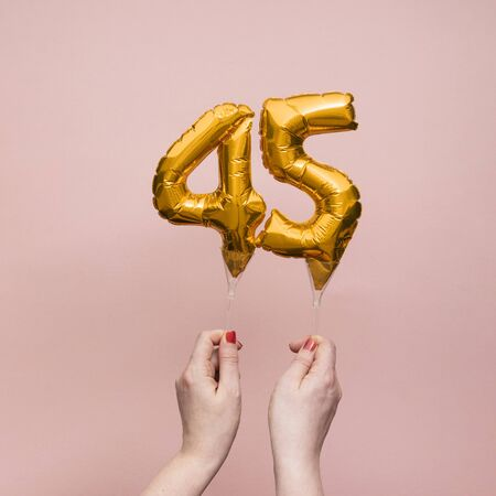 Female hand holding a number 45 birthday anniversary celebration gold balloon.