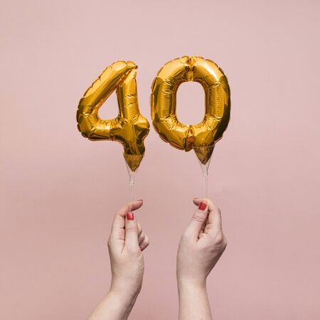 Female hand holding a number 40 birthday anniversary celebration gold balloon.