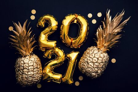 Happy new year 2021 gold foil balloon and pineapple celebration background.