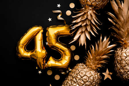 45th birthday celebration background with gold foil balloons and golden pineapples. 스톡 콘텐츠