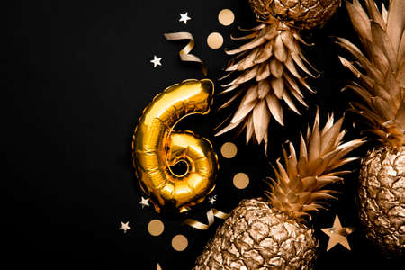 6th birthday celebration background with gold foil balloons and golden pineapples. 免版税图像