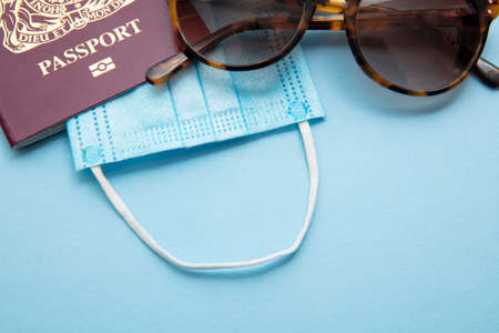 Summer travel during outbreak. Passport with face mask