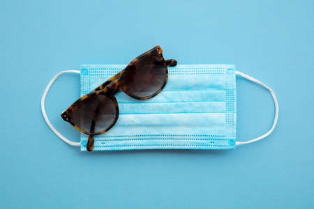 summer travel background. Medical mask with sunglasses Stock Photo
