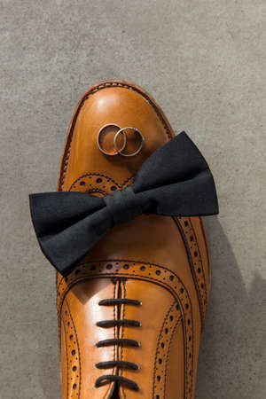 Bow tie and wedding rings on a brown leather grooms shoe