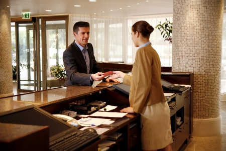 Man checking in at hotel reception desk photo