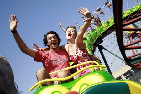 excitement: Teenage couple on roller coaster