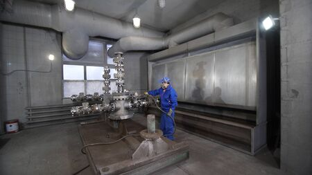 Worker in protective respirator paints oil and gas wellhead tree equipment with spray gun in production plant. Equipment for wellhead conncetion of oil and gas wells.
