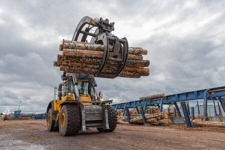 Ladeausrüstung für die Protokollierung. Baumstammlader für Holz, Baumstämme. Der Stammlader bewegt einen Stapel Kiefernstämme. Holzindustrie. Holzbearbeitungsfabrik.