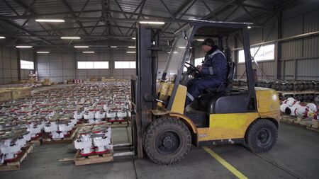Teamwork male person industry production, using machine work and vehicle, delivering merchandise for transnational export. Oil and Gas Wellhead tree equipment production plant on pallets in warehouse.