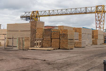 Wood factory stock and lumber board with nature business export. Stack of lumber wood in timber log storage. Wood processing joinery work wooden furniture. Wood timber construction material