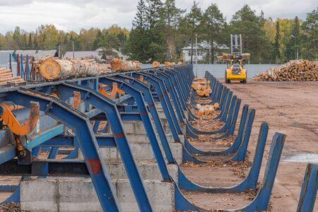 Línea de clasificación automática de troncos. Cargadora de ruedas y clasificación automática del diámetro de los troncos en el aserradero. Industria maderera Foto de archivo