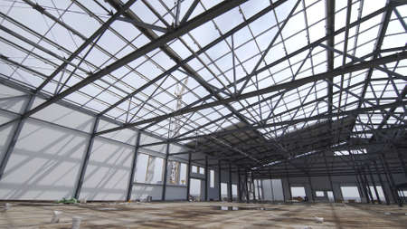 Construction of modern factory or warehouse, modern industrial exterior, panoramic view. Modern storehouse construction site, structural steel structure of new commercial building Archivio Fotografico