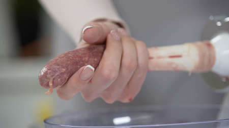 Woman cooks sausages in traditional way using sausage filler of electric mincer machine. Production of meat delicacies at home. Preparation of raw beef sausages with electric grinder. 版權商用圖片