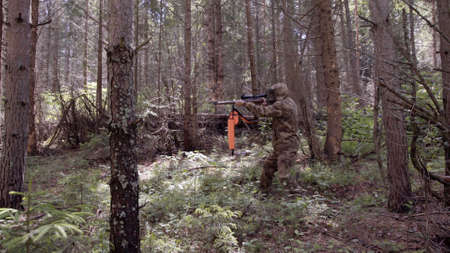 Man hunter takes aim with rifle. Men take aim. Man in comfortable camouflage clothes hunter outdoor in forest hunting alone. Hunter aiming down his rifle in summer season