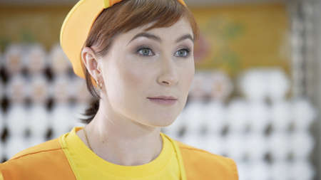 Portrait of smiling Caucasian female staff saleswoman talking to buyer and standing in grocery section of supermarket. Cheerful slender saleswoman in yellow t-shirt andorange apron.