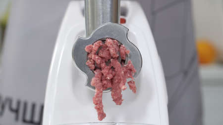 Filling comes out through raw meat grinder sieve. Grinder close up. Pile of chopped meat. Electric mincer machine with fresh chopped meat. Preparation of minced beef with an electric meat grinder.