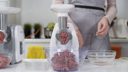 Making raw mincemeat with meat mincer at home. Pile of chopped meat. Electric mincer machine with fresh chopped meat. Preparation of minced beef with an electric meat grinder. Banco de Imagens
