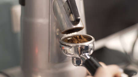 A barista woman picks up ground coffee from a coffee grinder in a holding