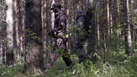 Two hunter men in camouflage clothes with guns walking through forest during hunting season. Man hunter outdoor in forest hunting. Male Tourists
