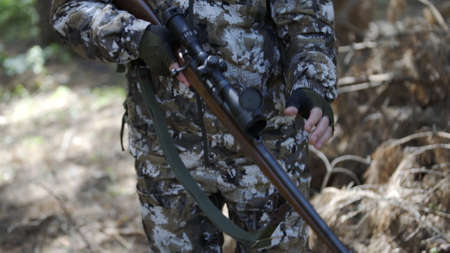 Hunter closes rifle scope and stands in forest and looks around. Outdoor activity concept. Summer hiking in wilderness area. Portrait of man hunter outdoor in forest hunting alone. Stockfoto
