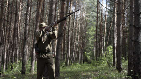 Man takes aim while standing from hunting rifle. Man in comfortable camouflage clothes hunter outdoor in forest hunting alone. Hunter in camouflage aims gun at object in forest during sunset.