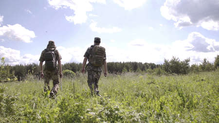 Rear view of two men walking with fishing poles in field to river. Relaxed men spending leisure together and going for fishing on river. View from back of walking men in camouflage with fishing rods.