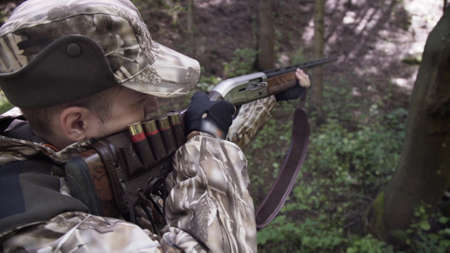 Man hunter takes aim with rifle. Men take aim. Man in comfortable camouflage clothes hunter outdoor in forest hunting alone. Stockfoto