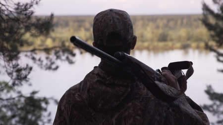 View from back of hunter in camouflage puts hunting rifle on his shoulder and looks at river from forest. Outdoor activity concept. Summer hiking in wilderness area.