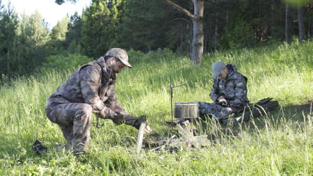 Man in camouflage clothes is chopping wood with axe and throwing it into bonfire. Tourist concept. Hunter checks or cleans hunting rifle. Best friends spend leisure weekend in forest nature background