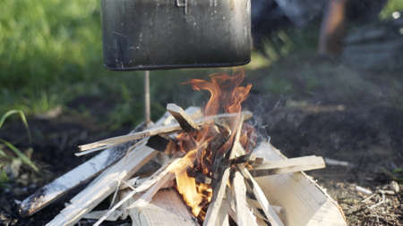 Black tourist pot hangs over burning flame of campfire in dark forest. Cooking dinner on wild hike. Cauldron of hot tea or food is heated over fire. Outdoor travel. Boil of hot meal in camp