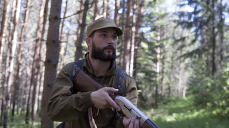 Hunting hunter men with gun walking through forest during hunting season. Man hunter outdoor in forest hunting alone. Hunter in camouflage aims gun at object inforest Stockfoto