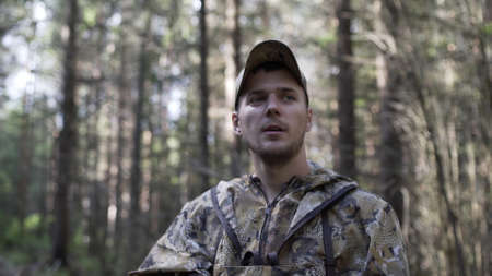 Portrait of handsome young man hunter or tourist. Man in camouflage clothes hunts outdoor in forest hunting alone. Close up of man hiker standing in forest. Hunter searching animal tracks.