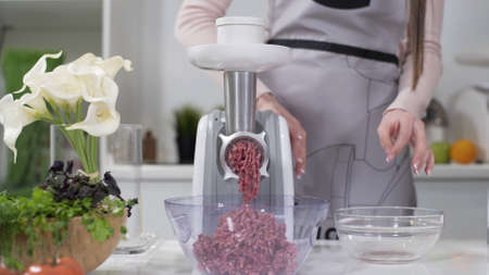Woman puts pieces of raw meat into electric meat grinder. Pile of chopped meat. Electric mincer machine with fresh chopped meat. Preparation of minced beef with an electric meat grinder.