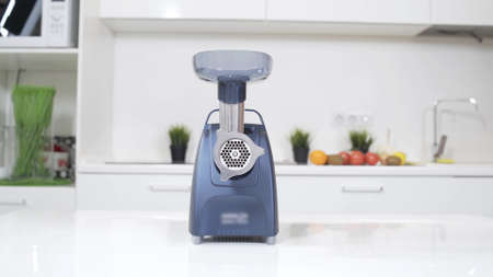 Blue electric mincer machines for minced meat on white table. Meat mincer of increased power is reliable assistant in kitchen. Making raw mincemeat with meat mincer at home.