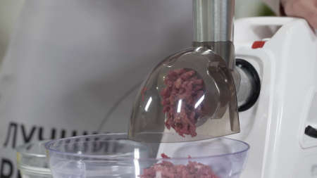 Making minced meat in an electric meat grinder from fresh beef at home. Pile of chopped meat. Electric mincer machine with fresh chopped meat. Preparation of minced beef with an electric meat grinder.