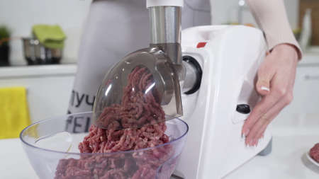Making minced meat in electric meat grinder from fresh beef at home. Electric mincer machine with fresh chopped meat. Preparation of minced beef with electric grinder. Written on apron: best recipes