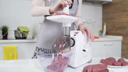 Making raw mincemeat with meat mincer at home. Pile of chopped meat. Electric mincer machine with fresh chopped meat. Preparation of minced beef with electric grinder. Written on apron: best recipes Stockfoto